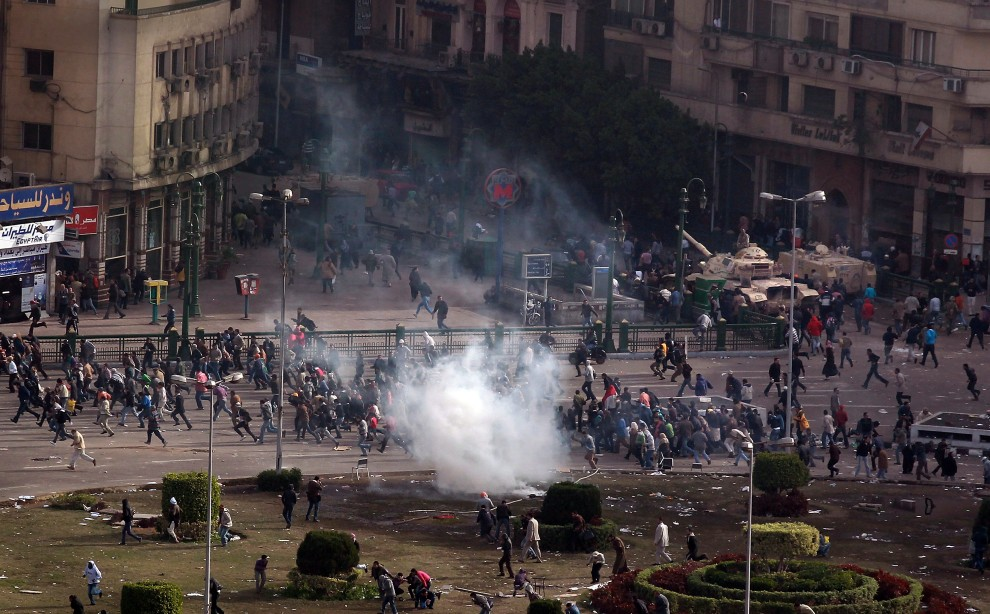 6. EGIPT, Kair, 29 stycznia 2011: Protestujący uciekają po tym, jak oddziały porządkowe wystrzeliły pojemniki z gazem łzawiącym. (Foto: Peter Macdiarmid/Getty Images)