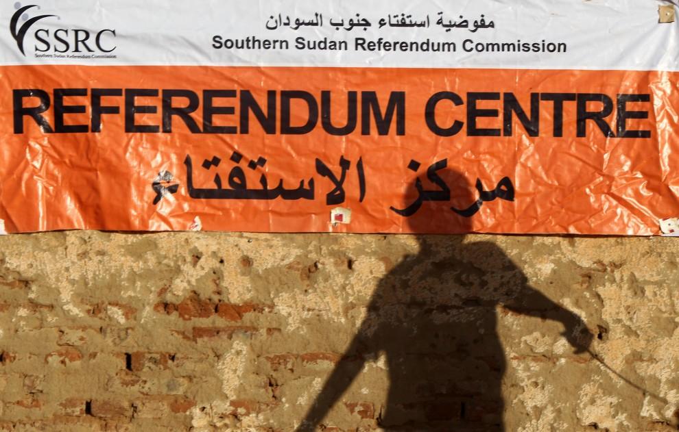 6. SUDAN, Chartum, 8 stycznia 2011: Cień chłopca padający na banner przy wejściu do punktu głosowania. AFP PHOTO/KHALED DESOUKI
