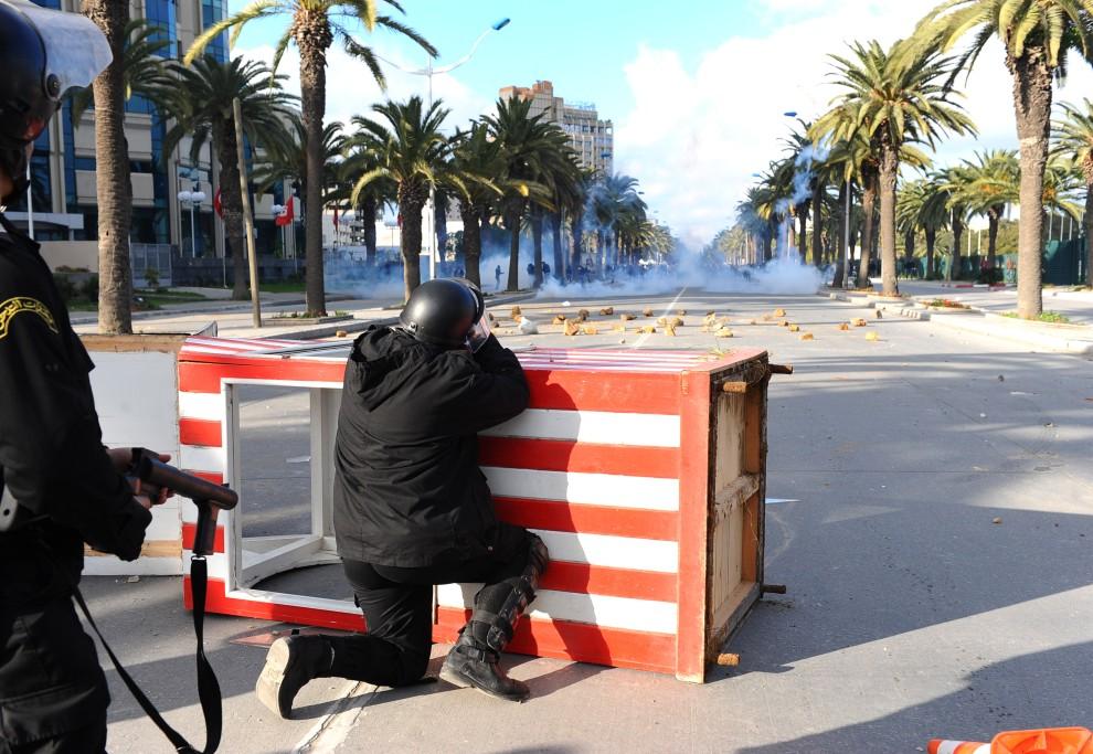 7. TUNEZJA, Tunis, 14 stycznia 2011: Funkcjonariusze służb bezpieczeństwa strzelają pojemnikami z gazem łzawiącym. AFP PHOTO / FETHI BELAID