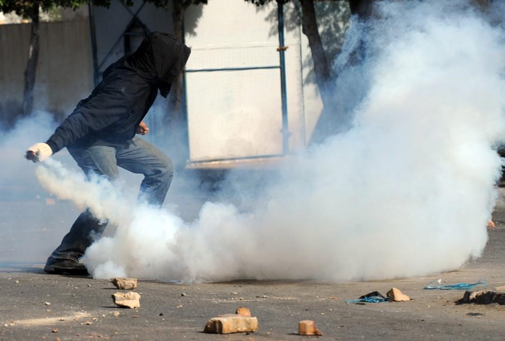 8. TUNEZJA, Regueb, 10 stycznia 2011: Demonstrujący mężczyzna odrzuca pojemnik z gazem łzawiącym. AFP PHOTO/STR