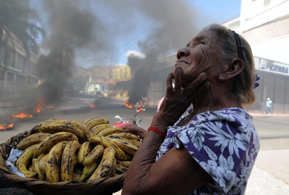 """9. HONDURAS, Tegucigalpa, 24 stycznia 2011: Kobieta sprzedająca banany w pobliżu opon podpalonych przez protestujących nauczycieli. Prezydent Porfirio Lobo   zawiesił na czas nieokreślony odpowiednik naszej """"Karty Nauczyciela. AFP PHOTO/Orlando SIERRA"""