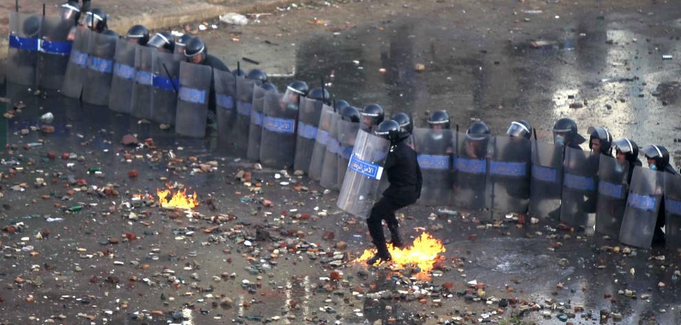 9. EGIPT, Suez, 27 stycznia 2011: Policjant, pod którego stopami rozbiła się butelka z łatwopalną substancją. AFP PHOTO/KHALED DESOUKI