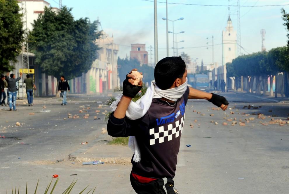 9. TUNEZJA, Regueb, 10 stycznia 2011: Młody Tunezyjczyk rzuca kamieniami w kierunku policjantów. AFP PHOTO/STR