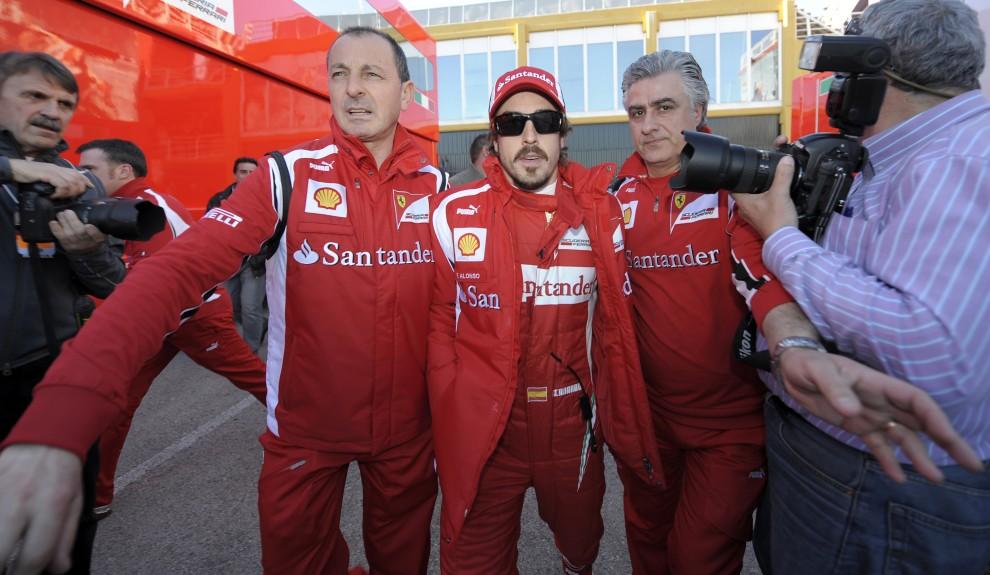 11. HISZPANIA, Walencja, 2 lutego 2011: Fernando Alonso eskortowany przez mechaników wchodzi na tor Ricardo Tormo. AFP PHOTO/ JAVIER SORIANO