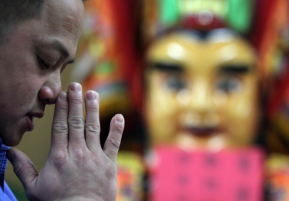 11. USA, San Francisco, 3 lutego 2011: Mężczyzna modli się w świątyni Ma-Tsu. (Foto: Justin Sullivan/Getty Images)