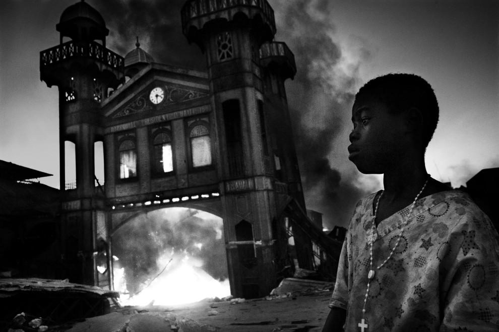"""11.HAITI, Port-au-Prince, 18 stycznia 2010: I nagroda World Press Photo w kategorii """"Wydarzenia w zbliżeniu - zdjęcia pojedyncze"""" za fotografię   przedstawiającą chłopca na tle płonącego budynku (Port-au-Prince, Haiti). AFP PHOTO / CONTRASTO / RICCARDO VENTURI"""