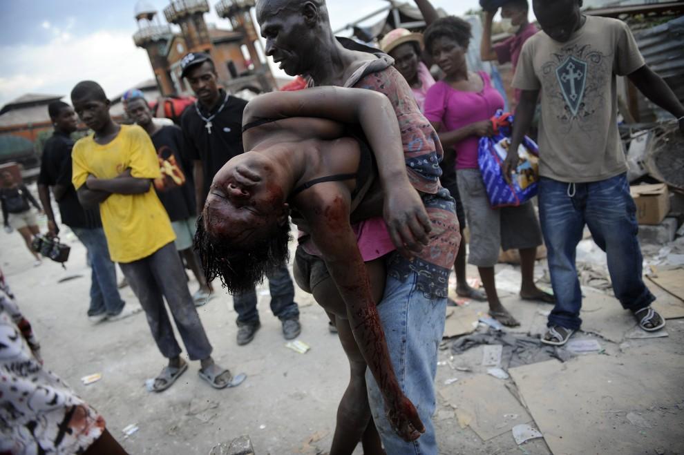 """12.HAITI, Port-au-Prince,19 stycznia 2010: Olivier Laban-Mattei, I nagroda w kategorii """"Wydarzenia -reportaż"""". Na zdjęciu Osam Cherisma niesie ciało   córki zabitej przez policjanta w trakcie rabowania pozostawionych dóbr. AFP PHOTO / OLIVIER LABAN-MATTEI"""