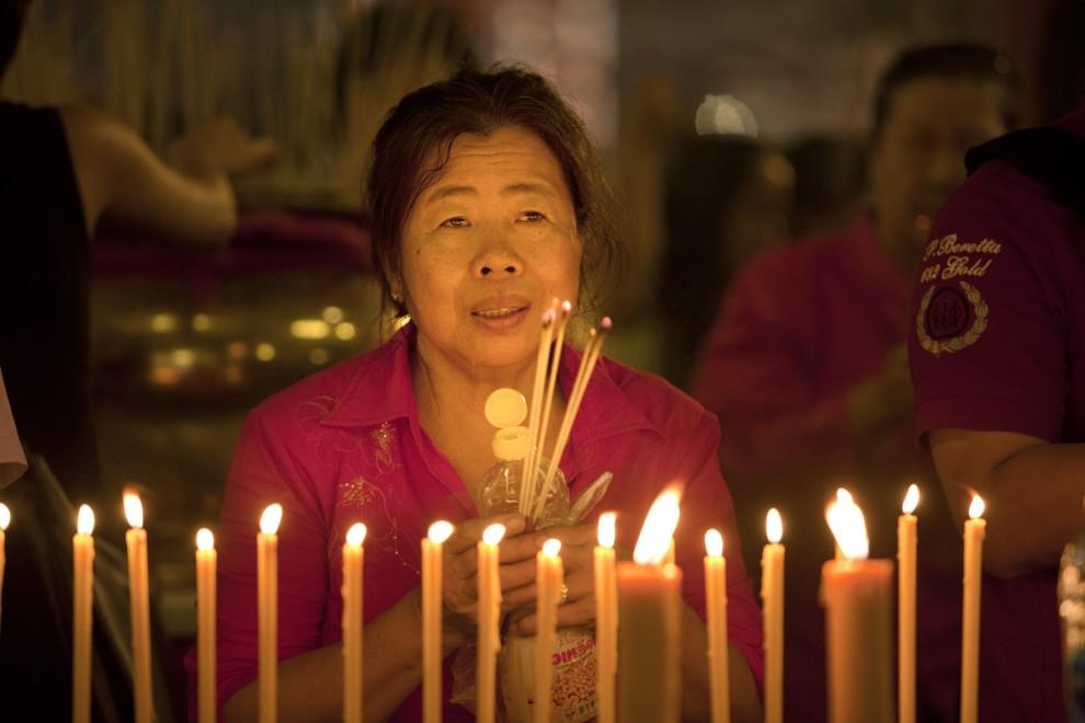 12. TAJLANDIA, Bangkok, 3 lutego 2011: Kobieta modli się w jednej ze świątyń w Bangkoku. (Foto: Paula Bronstein /Getty Images)