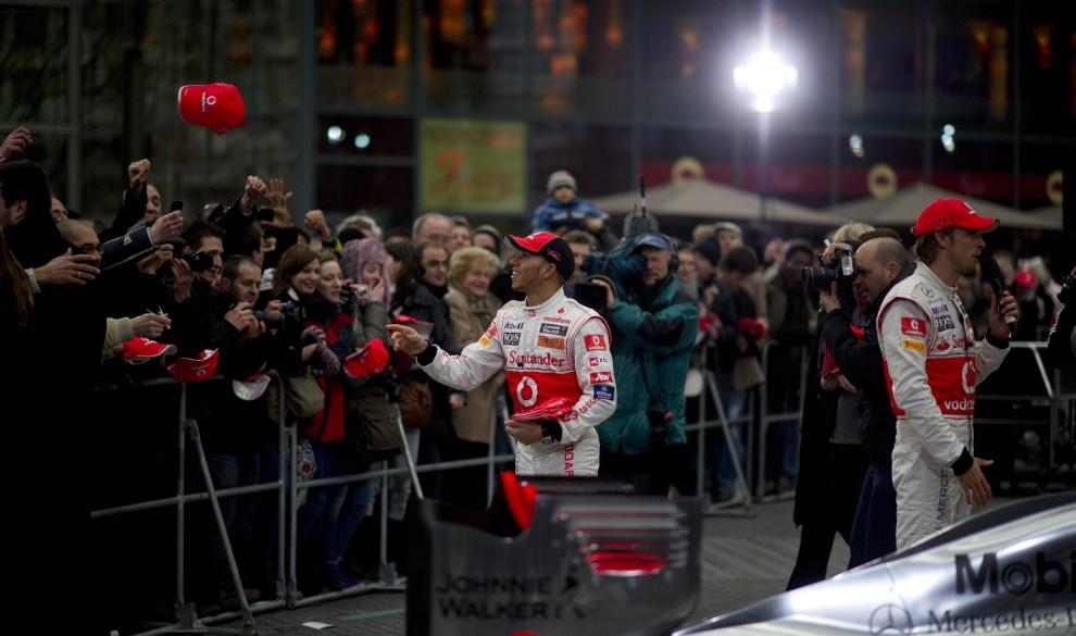 13. NIEMCY, Berlin, 4 lutego 2011:  Jenson Button (po prawej) i Lewis Hamilton (po lewej) rozdają gadżety swoim fanom. AFP PHOTO / JOHANNES EISELE