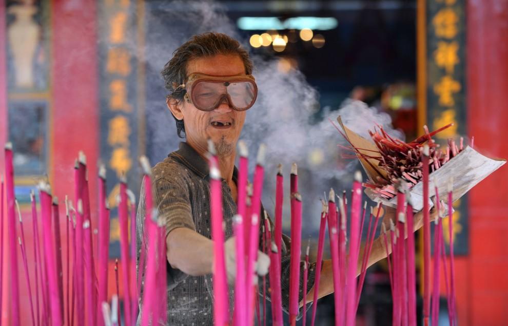 13. INDONEZJA, Dżakarta, 29 stycznia 2011: Mężczyzna zbiera wypalone kadzidła w świątyni Jin De Yuan. AFP PHOTO / ADEK BERRY