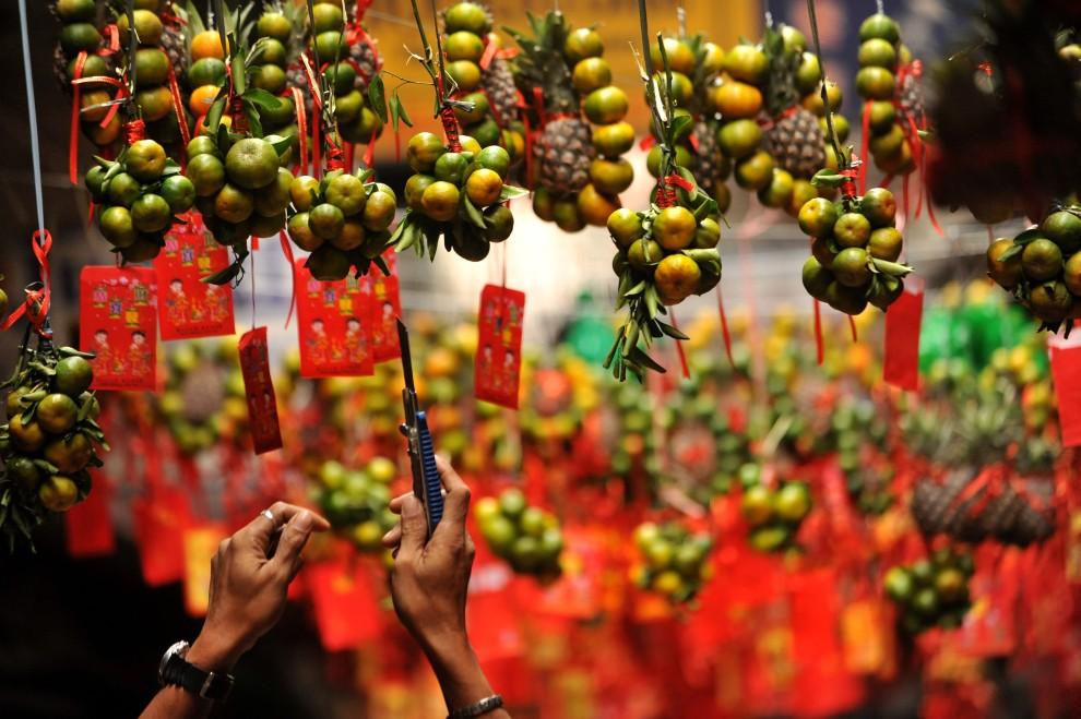 15. FILIPINY, Manila, 2 lutego 2011: Sprzedawca układa świąteczne kompozycje z owoców. AFP PHOTO/NOEL CELIS