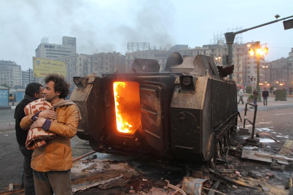16. EGIPT, Kair, 29 stycznia 2011: Mężczyzna stoi obok płonącego wojskowego transportera. AFP PHOTO/KHALED DESOUKI