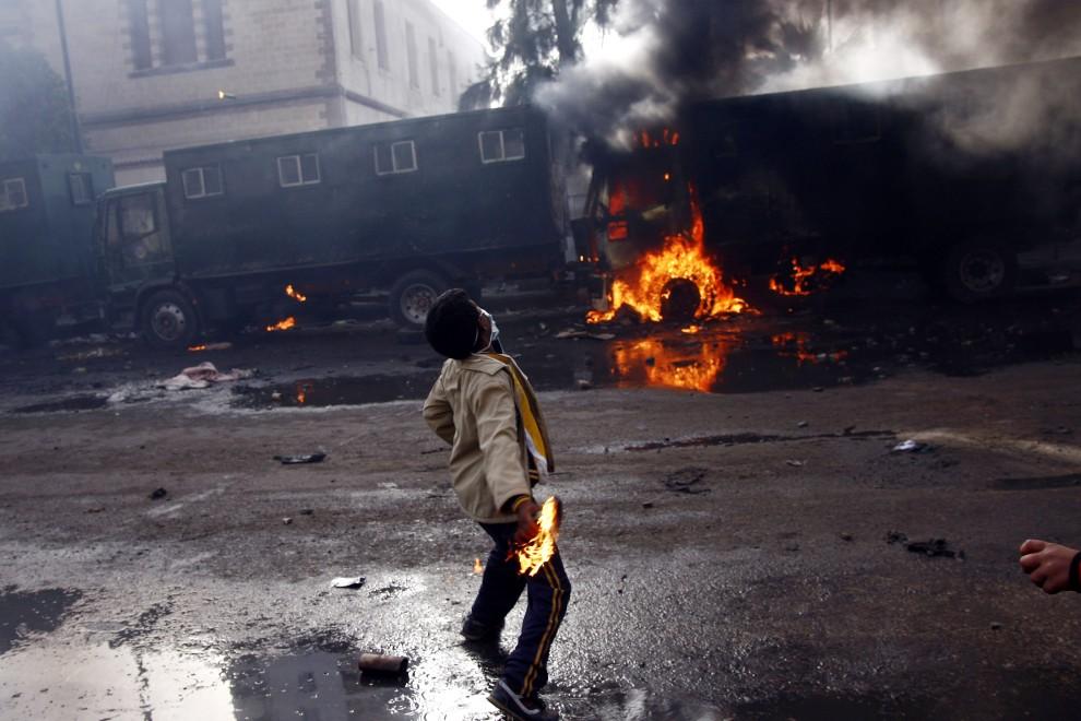 17. EGIPT, Suez, 28 stycznia 2011: Mężczyzna rzuca butelkę z łatwopalną cieczą w kierunku pojazdów policji. AFP PHOTO/STR