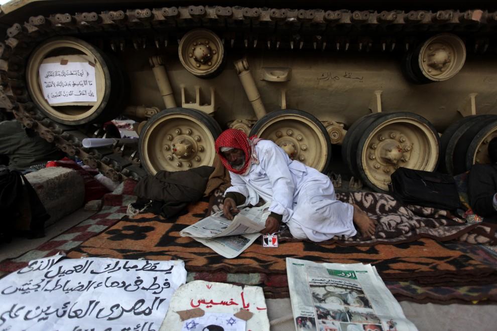 17. EGITP, Kair, 9 lutego 2011: Uczestnik demonstracji antyrządowych przegląda prasę w pobliżu czołgu zaparkowanego na głównym placu Kairu. AFP PHOTO/PATRICK BAZ