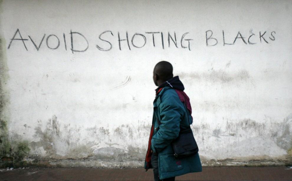 """18. WŁOCHY, Rosarno, 9 stycznia 2010: Imigrant przebywający nielegalnie we Włoszech przechodzi obok napisu  """"Avoid shooting Blacks"""" (ang. Unikajcie   strzelania do czarnych). W styczniu 2010 roku doszło do zamieszek pomiędzy lokalną ludnością i imigrantami. AFP PHOTO / Carlo Hermann"""