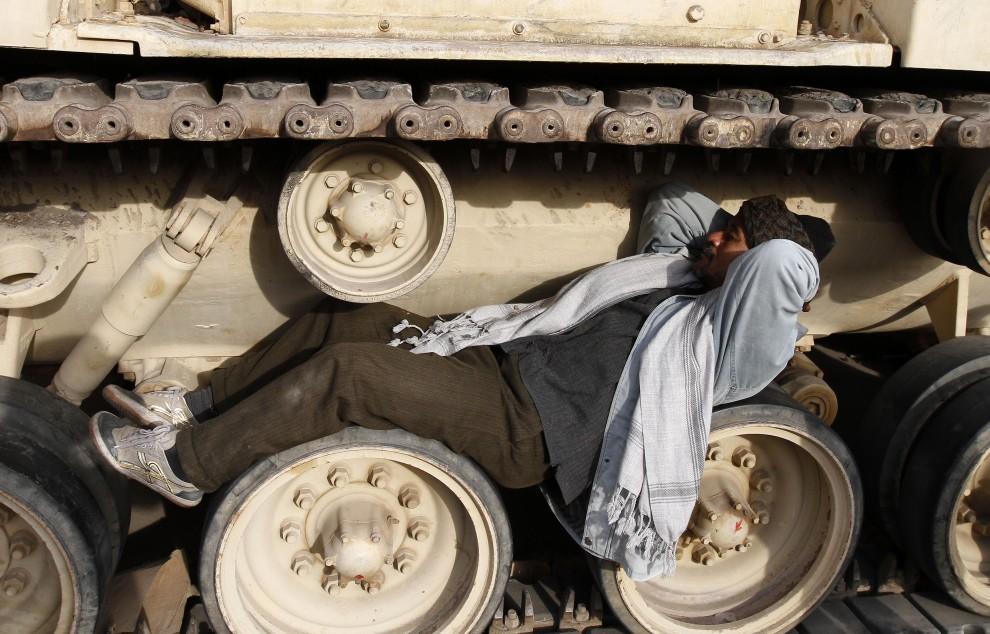 18. EGITP, Kair, 6 lutego 2011: Mężczyzna drzemie na kołach czołgu zaparkowanego na Tahrir. AFP PHOTO/MOHAMMED ABED