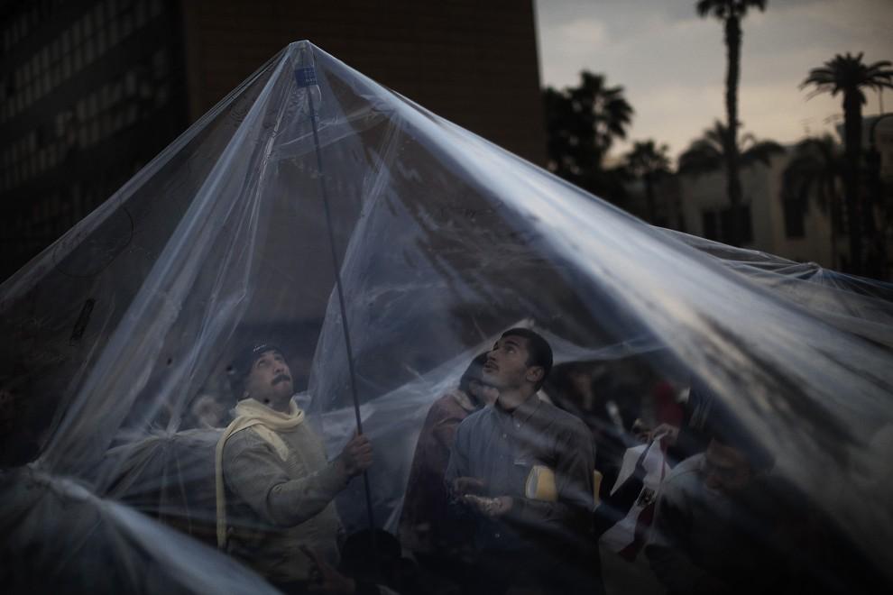 20. EGITP, Kair, 7 lutego 2011: Demonstranci rozkładają plastikowe siatki, które mają chronić ich przed zmianami pogody. AFP PHOTO/MARCO LONGARI