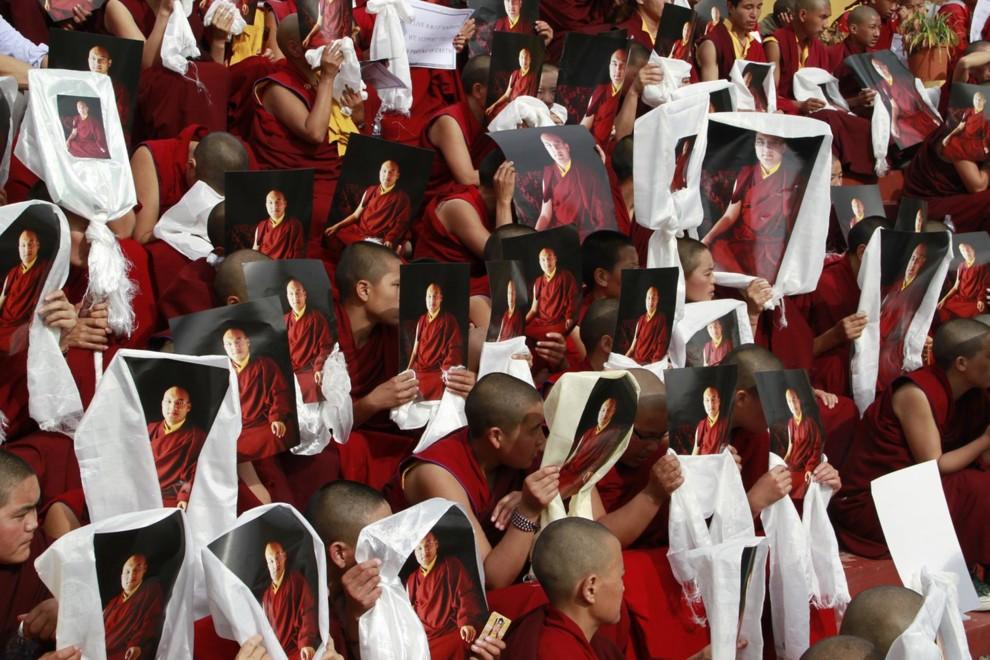 22. INDIE, Dharmshala, 2 lutego 2011: Tybetańscy mnisi trzymają plakaty z wizerunkiem  Karmapy – jednego z największych nauczycieli buddyzmu tybetańskiego. AFP PHOTO/LOBSANG WANGYAL