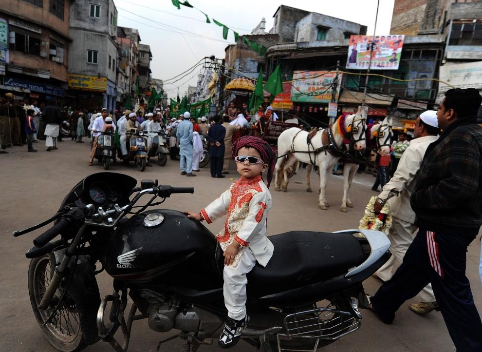 22. INDIE, New Delhi, 16 lutego 2011: Chłopiec na motocyklu przygląda się uczestnikom parady z okazji święta Eid Milad-un-Nabi. AFP PHOTO/MANAN VATSYAYANA