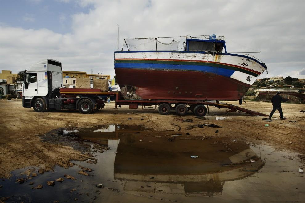 27. WŁOCHY, Lampedusa, 14 lutego 2011: Łódź tunezyjskich imigrantów usuwana z portu w Lampedusie. AFP PHOTO / ROBERTO SALOMONE