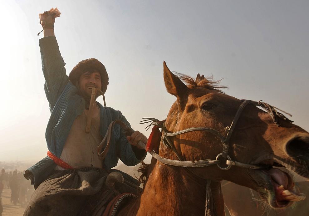 2. AFGANISTAN, Kabul, 8 stycznia 2010: Mężczyzna z pieniędzmi wygranymi za zwycięstwo w buzkaszi. AFP PHOTO/Massoud HOSSAINI