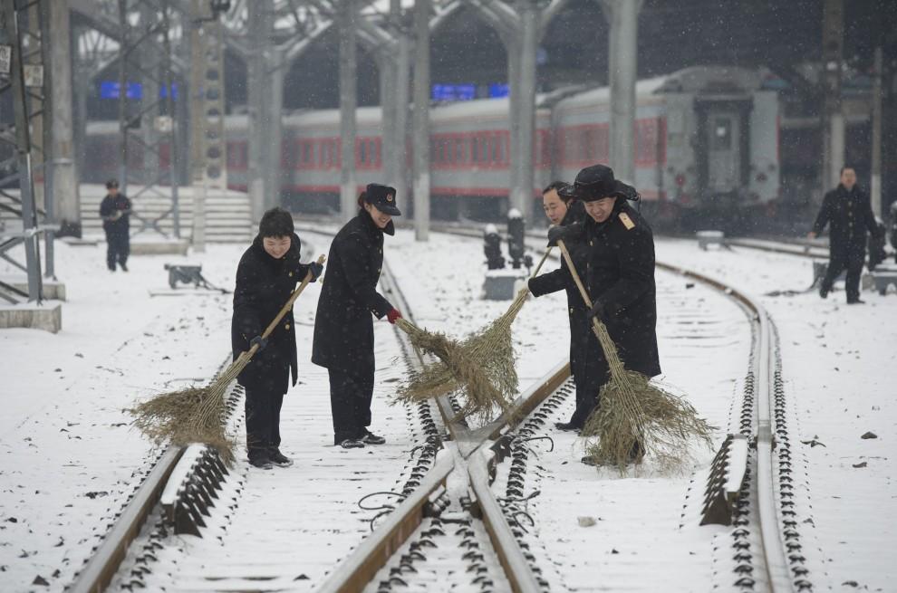 30. CHINY, Pekin, 10 lutego 2011: Pracownicy kolei odmiatają śnieg z torów. AFP PHOTO