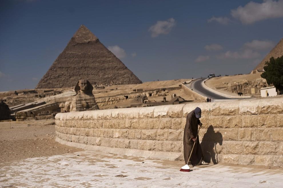 31. EGIPT, Giza, 14 lutego 2011: Mężczyzna zamiata wejście dla turystów zwiedzających piramidy. AFP PHOTO/PEDRO UGARTE