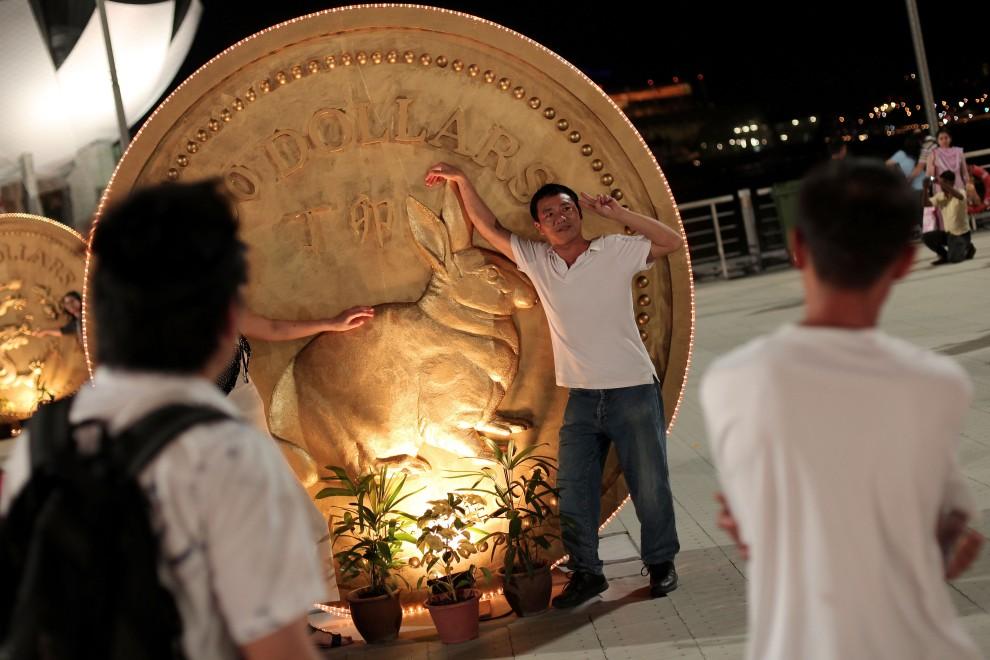 34. SINGAPUR, 2 lutego 2011: Mężczyzna pozuje do zdjęcia z symbolem nadchodzącego roku. (Foto: Chris McGrath/Getty Images)