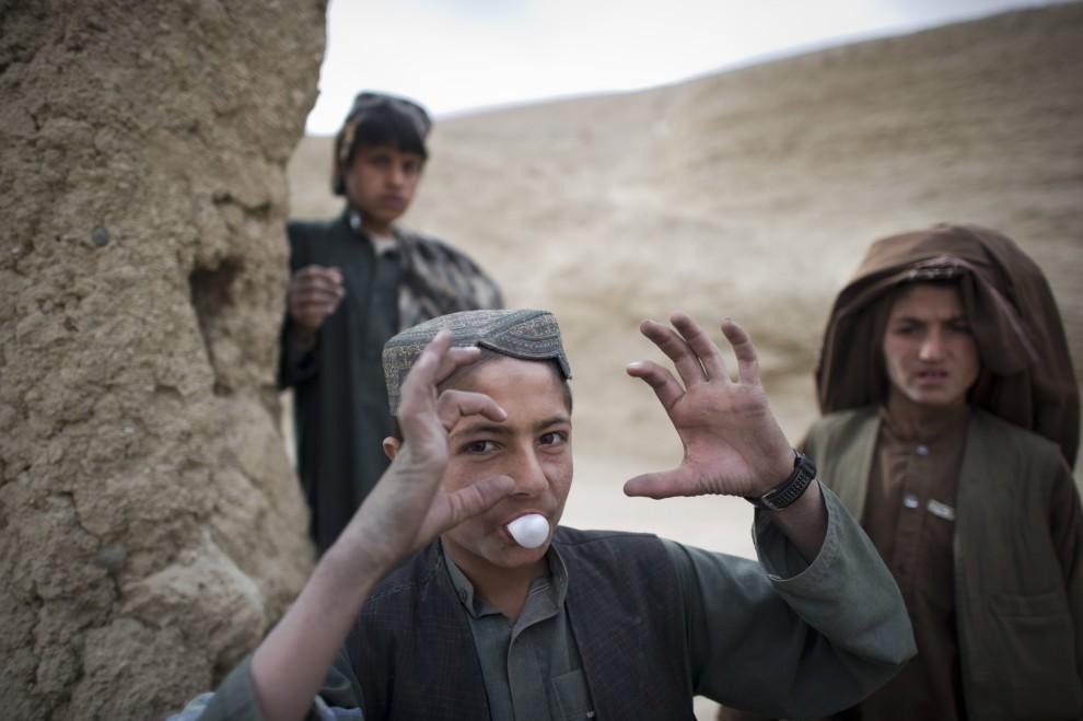 4. AFGANISTAN, Musa Qala, 28 stycznia 2011: Afgańscy chłopcy przyglądają się patrolującym okolicę żołnierzom. AFP PHOTO / DMITRY KOSTYUKOV