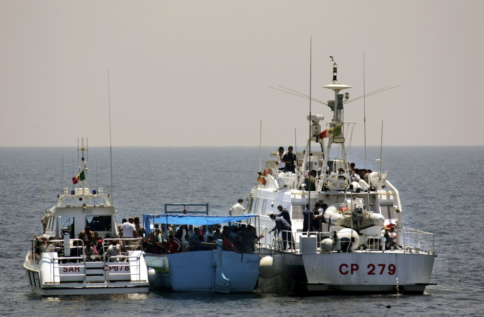 4. WŁOCHY, Lampedusa, 21 czerwca 2005: Straż przybrzeżna podejmuje z pokładu łodzi imigrantów. (Foto: Marco Di Lauro/Getty Images)