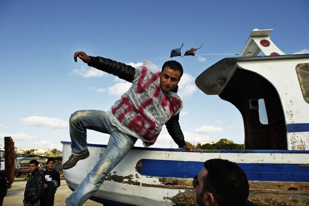 """5. WŁOCHY, Lampedusa, 11 lutego 2011: Tunezyjczyk w koszulce z napisem """"Hooray for Italy!"""" zeskakuje z łodzi, która przybiła do portu w Lampedusie. AFP PHOTO / ROBERTO SALOMONE"""