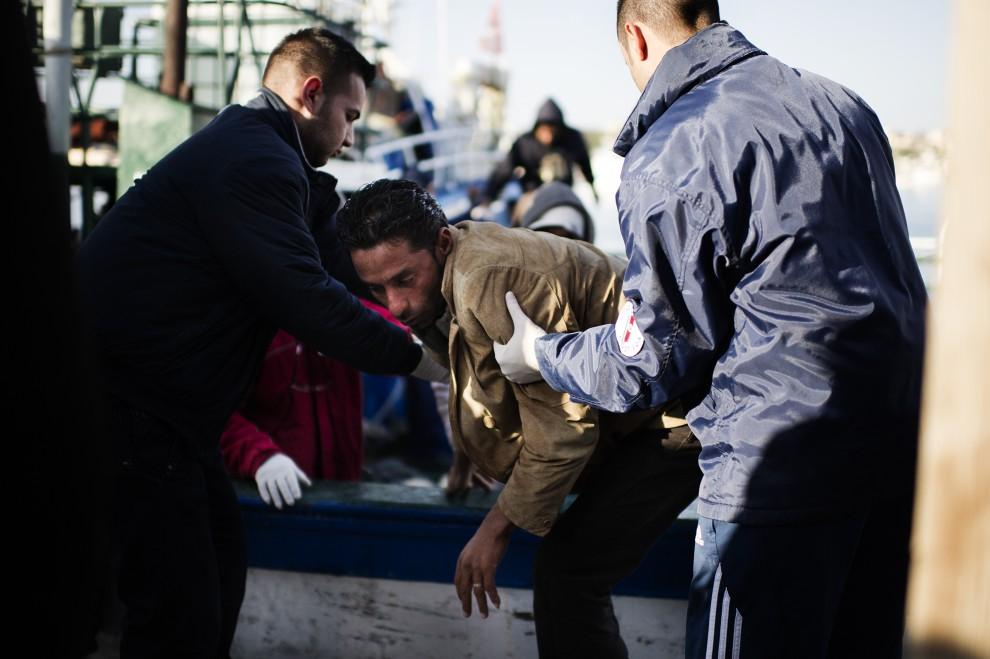 6. WŁOCHY, Lampedusa, 13 lutego 2011: Funkcjonariusze pomagają zejść z pokładu imigrantowi z Tunezji. AFP PHOTO / ROBERTO SALOMONE