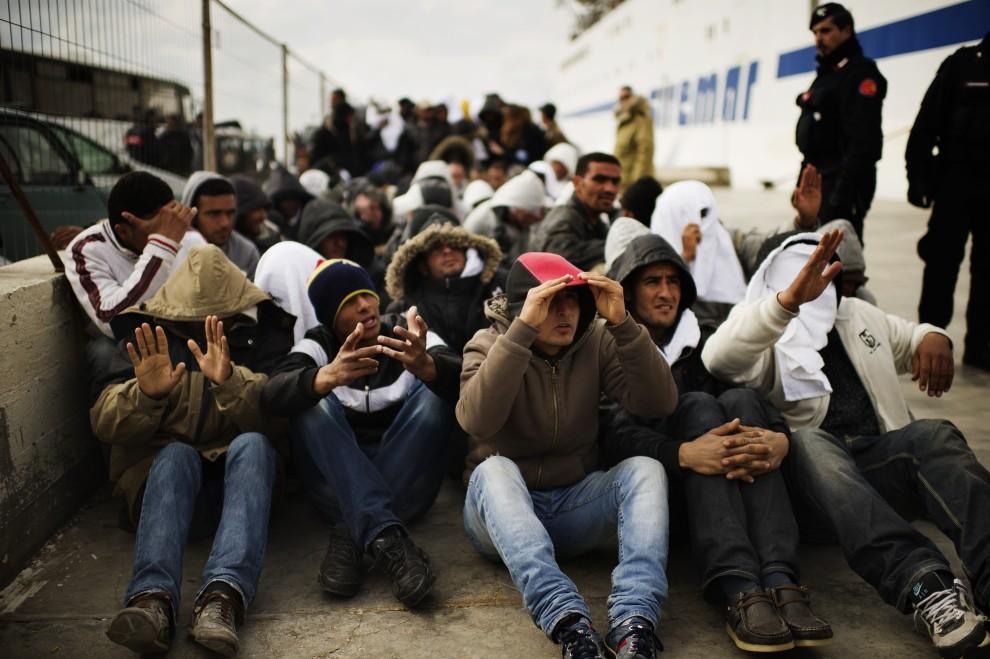 7. WŁOCHY, Lampedusa, 14 lutego 2011: Tunezyjczycy czekają na przewiezienie ich do centrum dla uchodźców. AFP PHOTO / ROBERTO SALOMONE