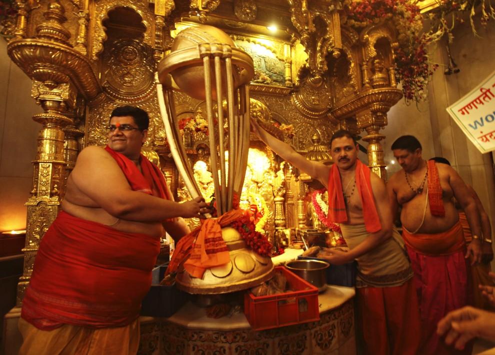 7. INDIE, Bombaj, 17 lutego 2011: Kapłani trzymają replikę pucharu mistrzostw świata w krykiecie, podczas nabożeństwa religijnego. AFP PHOTO/STR