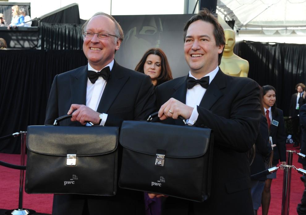 7. USA, Hollywood, 27 lutego 2011: Rick Ross (po lewej) i Brad Oltmann (po prawej) z firmy Price Waterhouse Cooper trzymają walizki z kopertami i nazwiskami zwycięzców. AFP PHOTO / MARK RALSTON