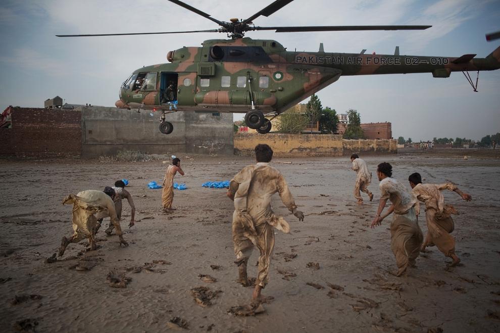 """8.PAKSITAN, Dadu, 13 września 2010: Austriak Daniel Berehulak zdobył I nagrodę World Press Photo w kategorii """"Ludzie i wydarzenia - reportaż"""" za zdjęcie pokazujące ofiary powodzi w Pakistanie, biegnące po jedzenie zrzucane z helikopterów. AFP PHOTO / GETTY IMAGES / DANIEL BEREHULAK"""