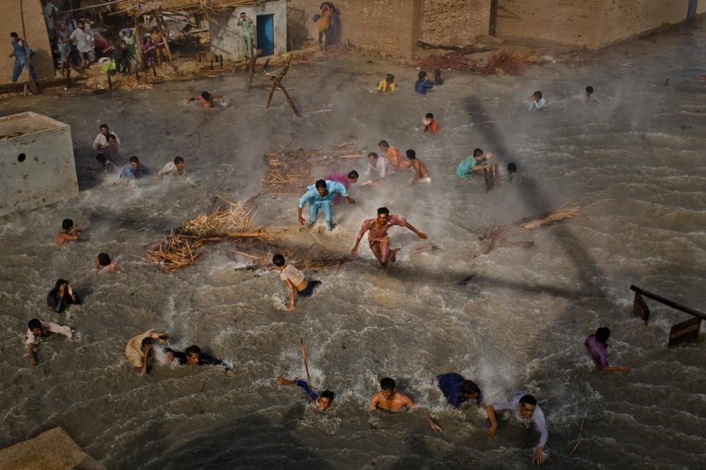 """9.PAKSITAN, Dadu, 13 września 2010: Austriak Daniel Berehulak zdobył I nagrodę World Press Photo w kategorii """"Ludzie i wydarzenia - reportaż"""" za   zdjęcie pokazujące ofiary powodzi w Pakistanie, biegnące po jedzenie zrzucane z helikopterów. AFP PHOTO / GETTY IMAGES / DANIEL BEREHULAK"""