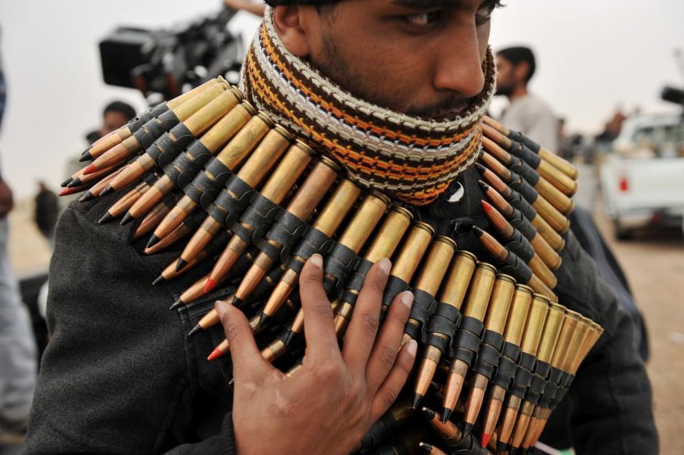 10. LIBIA, Ras Lanuf, 4 marca 2011: Opozycjonista z przerzuconym pasem amunicji. AFP PHOTO / ROBERTO SCHMIDT