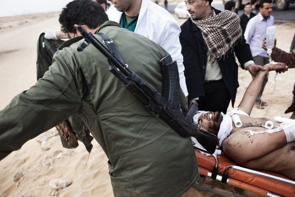 10. LIBIA, Ras Lanuf, 10 marca 2011: Rebeliant ewakuowany z pola walki. AFP PHOTO / MARCO LONGARI