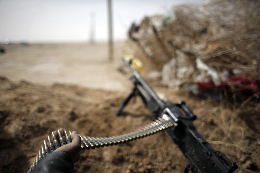 11. LIBIA, Adżdabija, 2 marca 2011: Jeden z powstańców na stanowisku ogniowym. AFP PHOTO / MARCO LONGARI