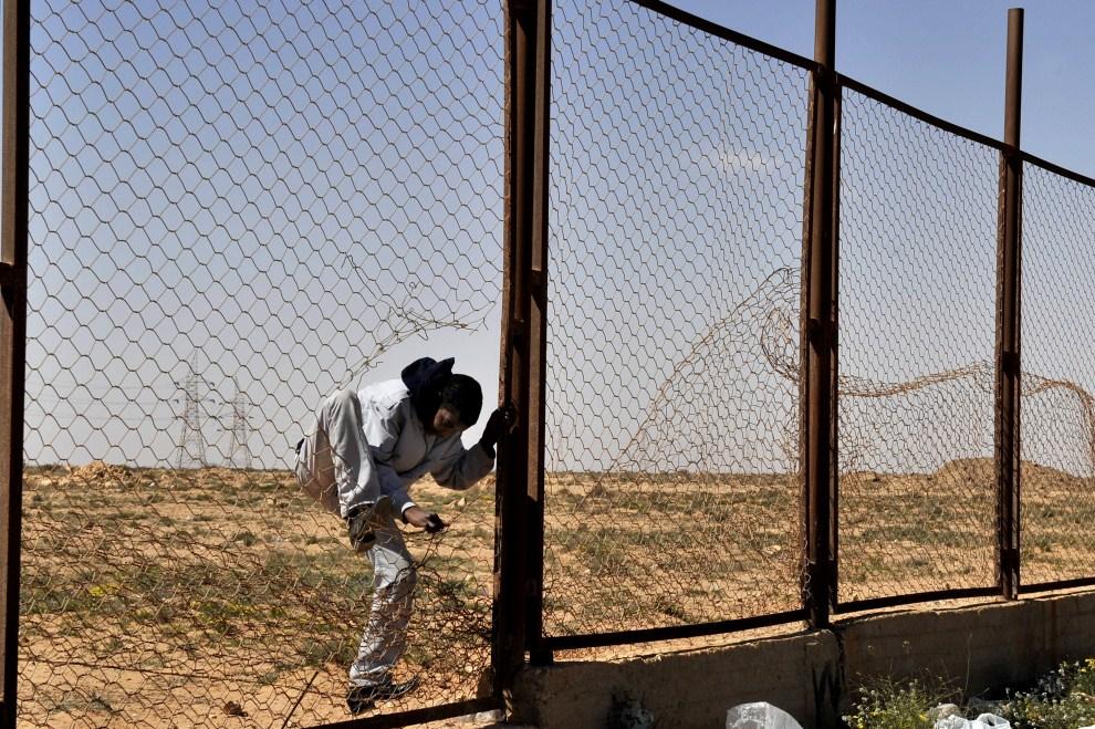 11. EGIPT, Sallum, 16 marca 2011: Uciekinier przedostaje się na pas ziemi niczyjej pomiędzy Egiptem i Libią. AFP PHOTO / ARIS MESSINIS