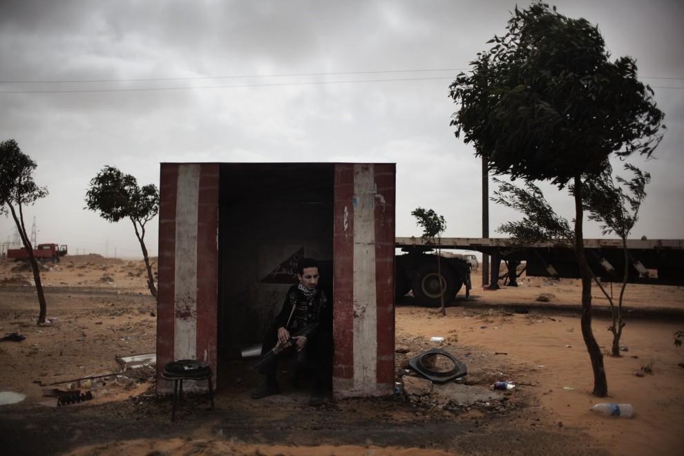 14. LIBIA, Ras Lanuf, 5 marca 2011: Uzbrojony powstaniec w pobliżu punktu kontrolnego. AFP PHOTO / MARCO LONGARI