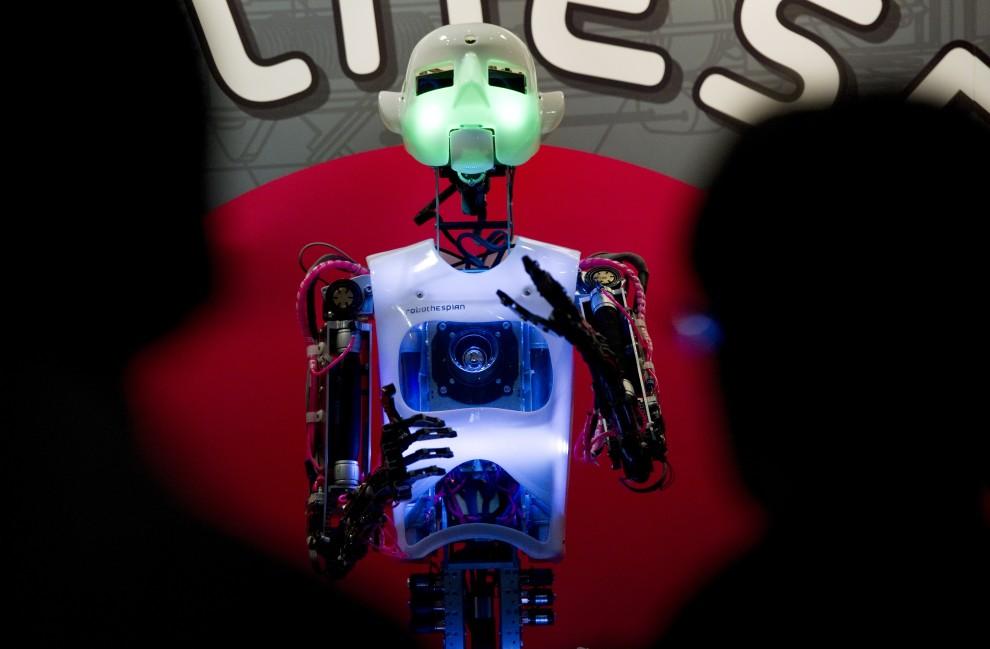 """15. NIEMCY, Hanower, 1 marca 2011: Zwiedzający targi CeBIT IT oglądają humanoida nazwanego """"RoboThespian"""". AFP PHOTO / JOHANNES EISELE"""