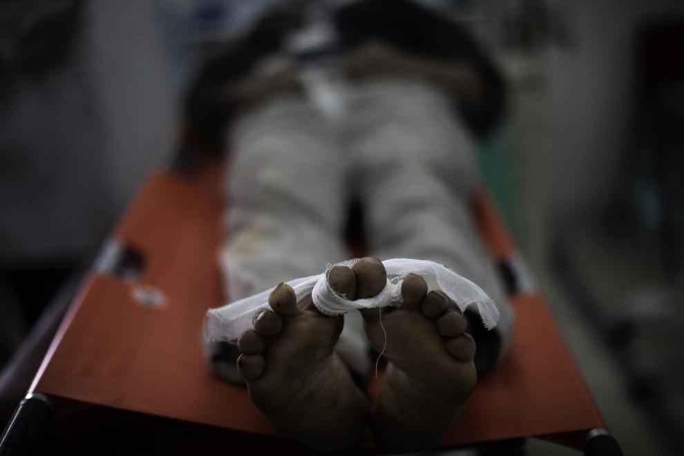 15. LIBIA, Ras Lanuf, 9 marca 2011: Ciało rebelianta zabitego podczas walk z oddziałami wiernymi Muammarowi Kadafiemu. AFP PHOTO/MARCO LONGARI
