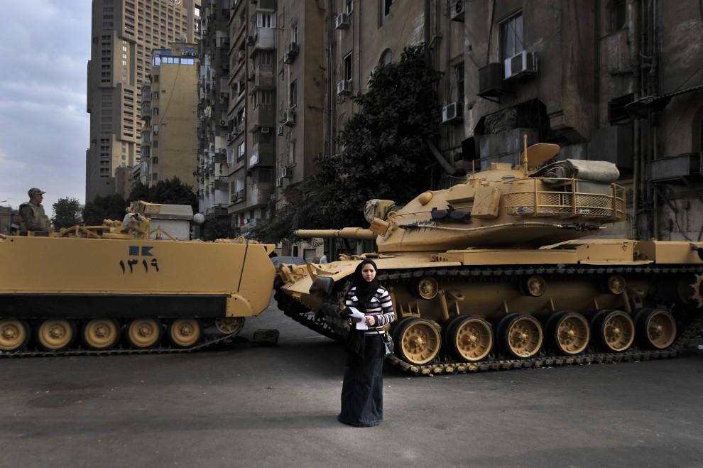 17. EGIPT, Kair, 10 marca 2011: Egipcjanka stoi przed czołgami blokującymi ulicę przed budynkiem telewizji. AFP PHOTO / ARIS MESSINIS