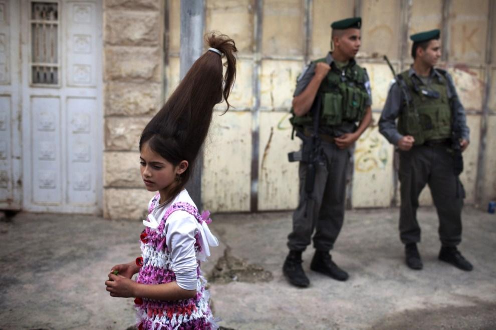 17. ZACHODNI BRZEG, Hebronn, 20 marca 2011: Izraelscy żołnierze obserwują ludzi świętujących Purim. AFP PHOTO/MENAHEM KAHANA