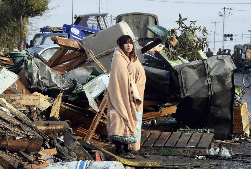 1. JAPONIA, Ishinomaki, 13 marca 2011: Dziewczyna otulona kocem przygląda się szkodom wyrządzonym przez trzęsienie ziemi i tsunami.  AFP PHOTO / YOMIURI   SHIMBNUN