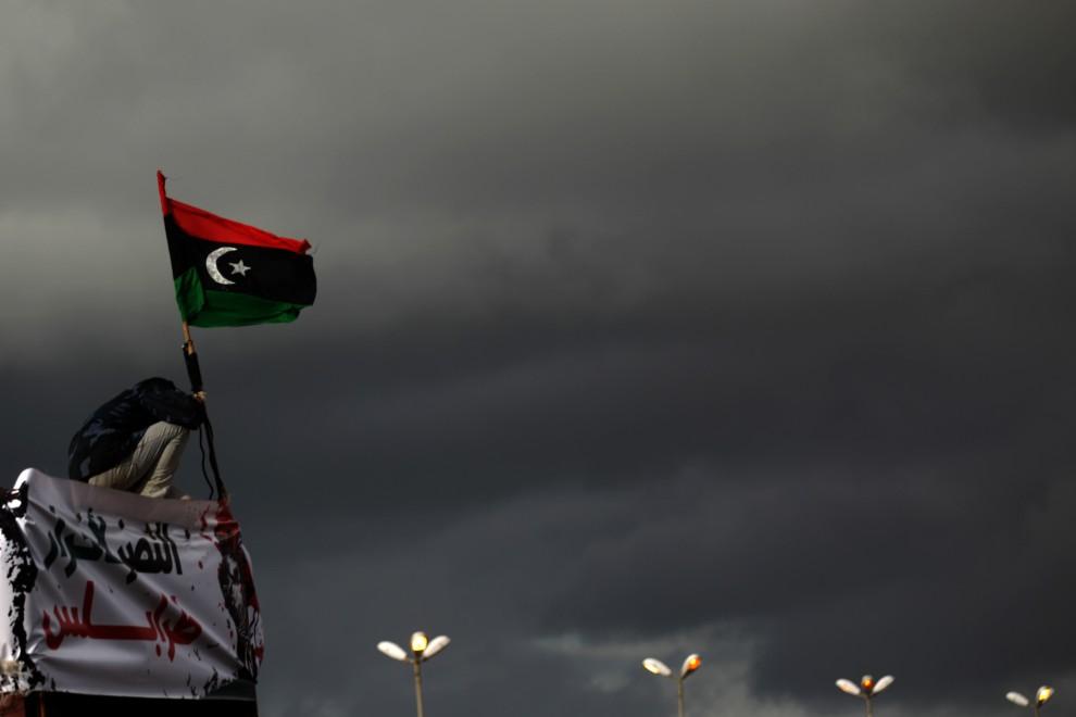 1. LIBIA, Benghazi, 27 lutego 2011: Przeciwnik Muammara Kadafiego wciąga na maszt dawną flagę Libii. AFP PHOTO/PATRICK BAZ