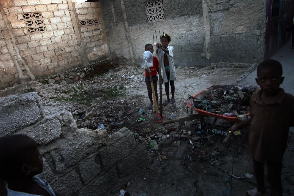 20. HAITI, Port-au-Prince, 1 marca 2011: Dzieci uprzątają pozostałości zniszczonego domu. AFP PHOTO / Hector RETAMAL