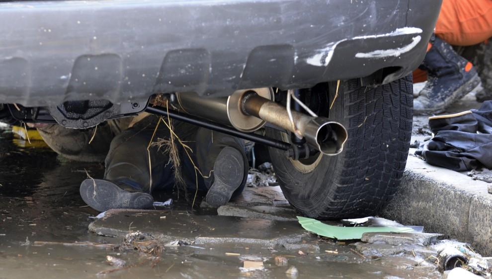 21. JAPONIA, Tagajo, 13 marca 2011: Ciało mężczyzny przygniecionego przez samochód. AFP PHOTO / KAZUHIRO NOGI